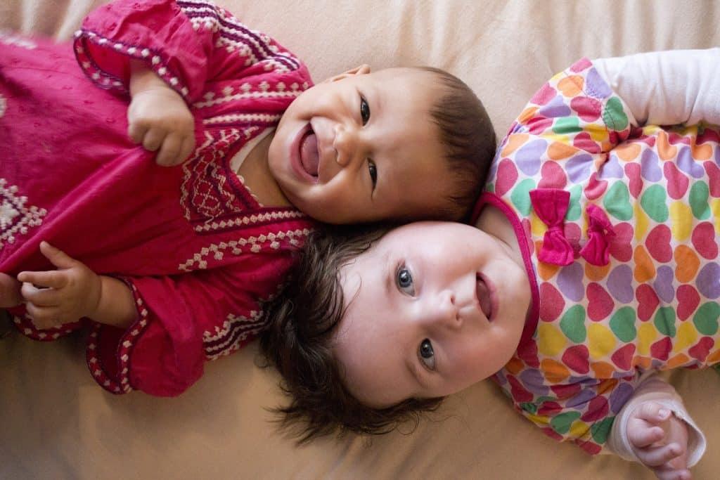 Imagem de duas bebês sorrindo e deitadas sobre uma cama.