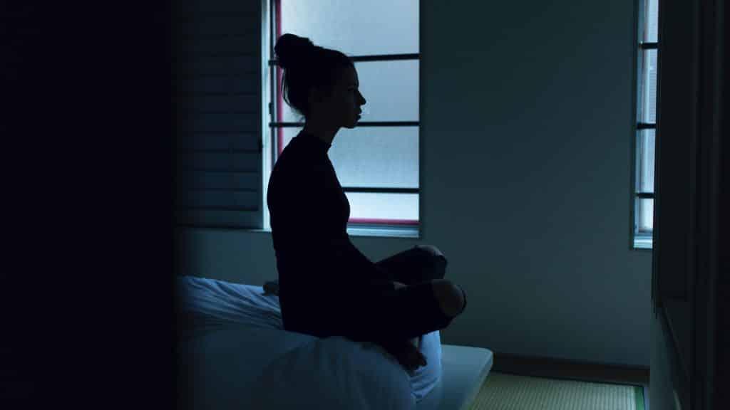 Mulher sentada na cama com o quarto escuro