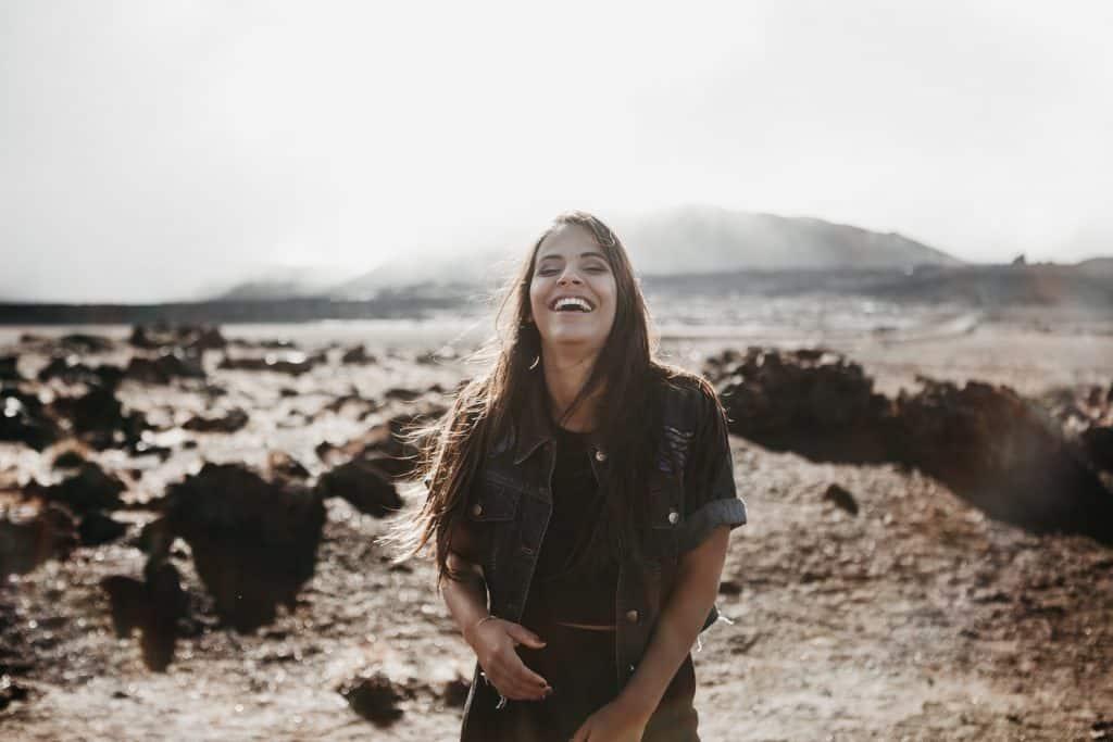 Mulher branca sorrindo meio a cenário caatinga