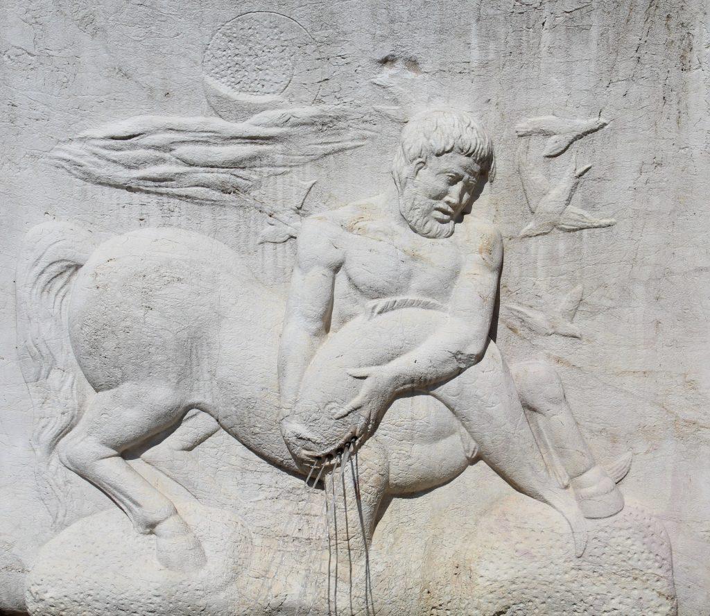 Imagem de um centauro: ser metade homem, metade cavalo, segurando um peixe.