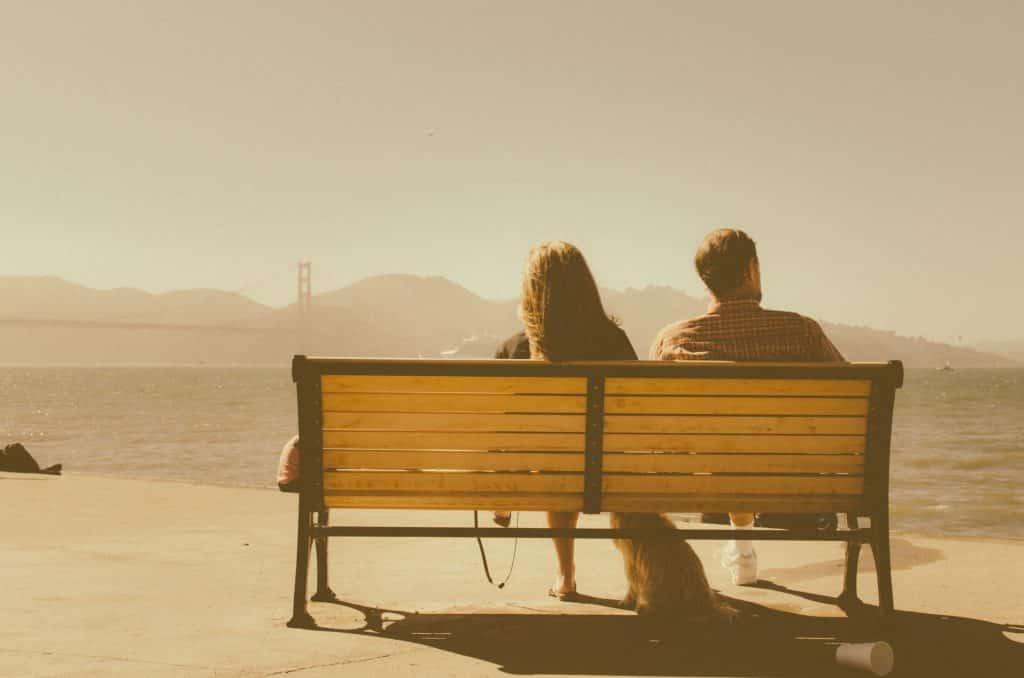 Homem e mulher sentados em um banco olhando para o mar