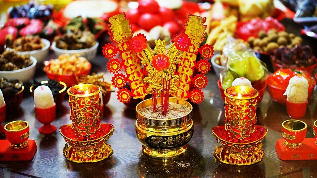 Imagem de vários itens como frutas, doces, velas nas cores vermelho e dourado representando a adoração para celebrar o ano novo chinês.