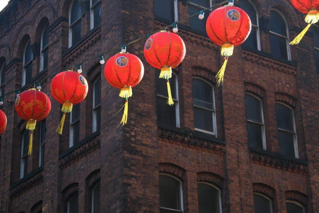 Imagem de fundo de um prédio marrom e uma rua decorada com lanternas vermelhas representando a comemoração do ano novo chinês.