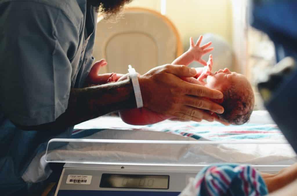 Homem colocando um bebê recém nascido em uma balança própria para a pesagem do mesmo.