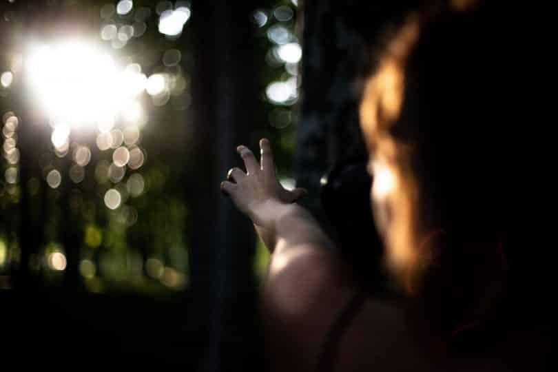 Mulher com a mão esticada em direção ao sol entre as árvores