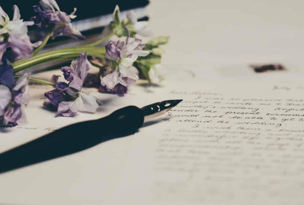 Carta em uma mesa com caneta e flores