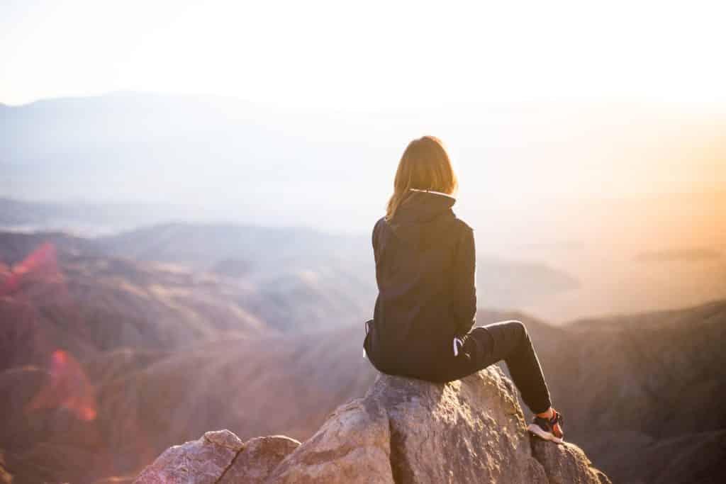 Mulher sentada no topo de uma pedra olhando as montanhas no nascer do sol