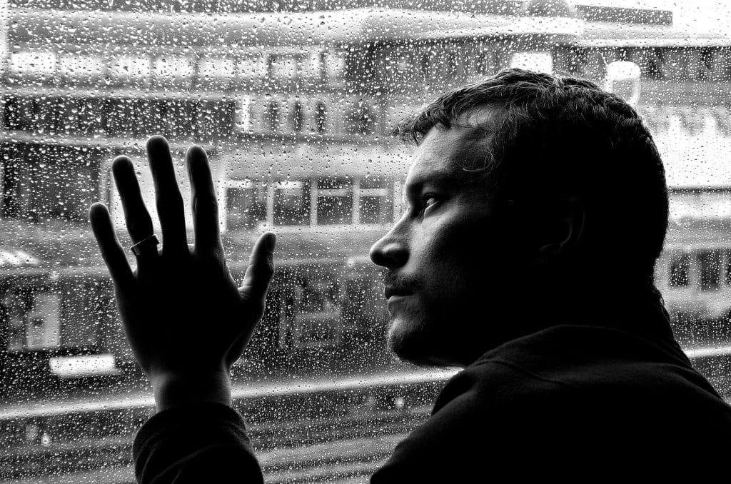Imagem preto e branco de um homem solitário e depressivo olhando para a janela em um dia chuvoso.