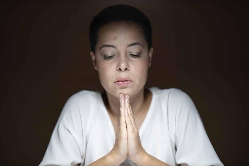 Mulher com os olhos fechados e as mãos unidas, rezando.