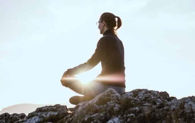 Mulher sentada em posição de lótus em pedra com sol refletindo e céu ao fundo