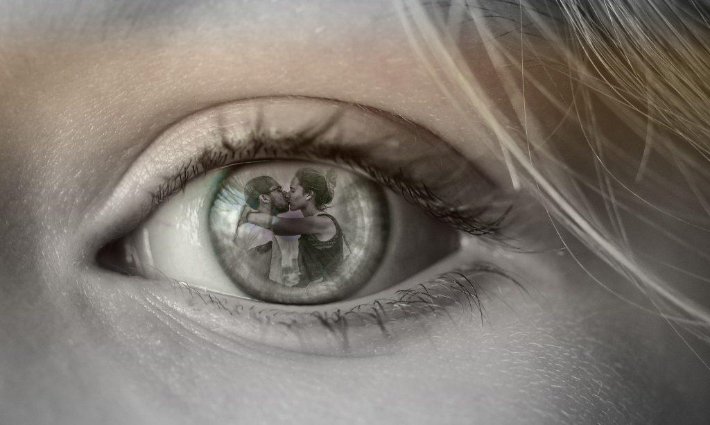 Olho de mulher refletinho um casal de homem e mulher se beijando