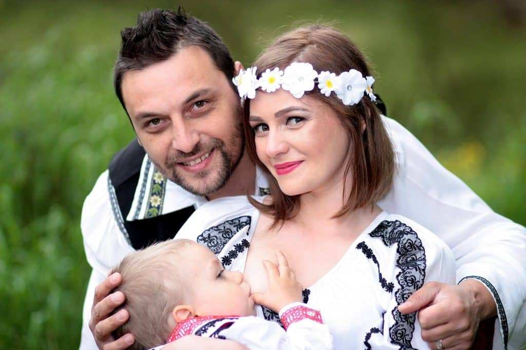 Imagem de um casal e o seu bebê. A mãe está amamentando o seu filho. Ela usa uma tiara de flores e todos estão felizes.
