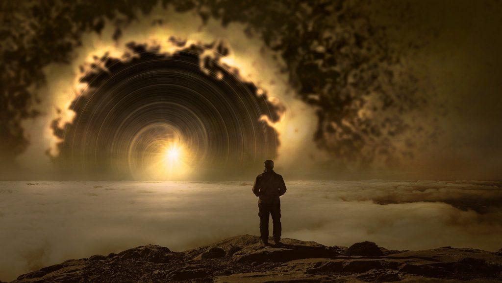 Homem de costas no pico de uma montanha em cima das nuvens diante de um fenômeno iluminado no céu.
