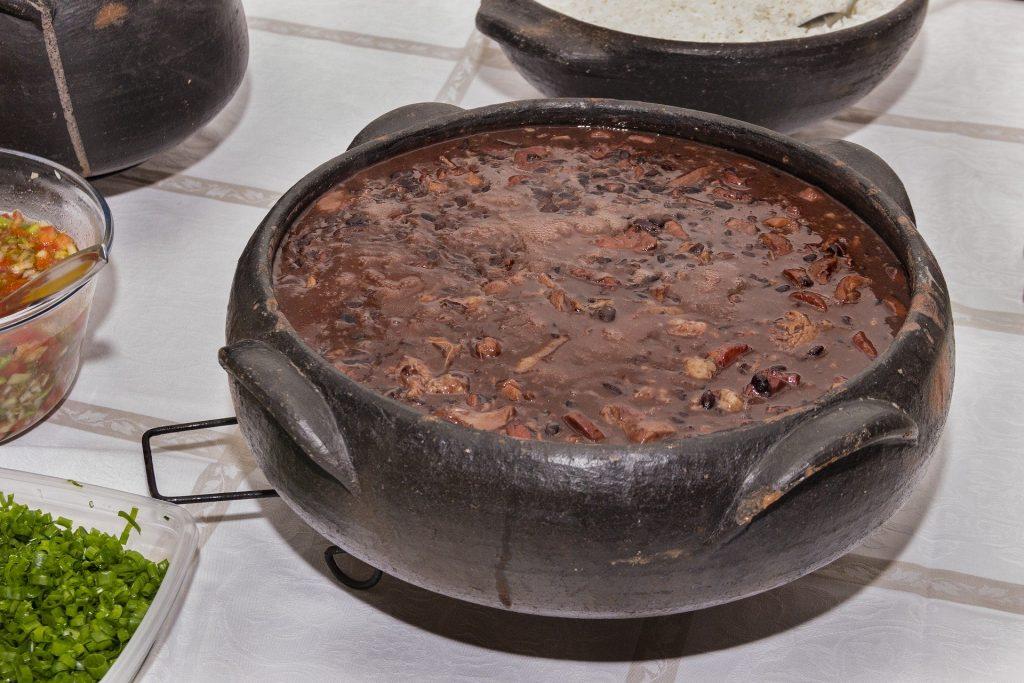 Imagem de uma linda e saborosa feijoada vegetariana disposta em uma cumbuca de barro sobre uma mesa.