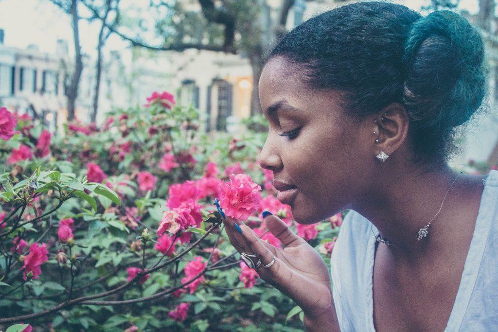 Imagem de uma linda mulher negra, feliz e com a autoestima elevada. Ela está cheirando uma linda flor cor de rosa.