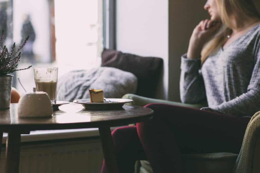 Mulher em uma cafeteria olhando para fora da janela com uma mesa em sua frente
