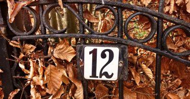 Imagem de um portão de ferro e nele está fixado o número 12.