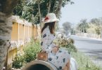 Imagem de uma garota bem vestida e elegante. Ele está sentada olhando para rua. Parece estar bem desanimada.