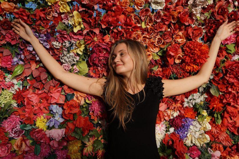 Imagem de uma linda mulher, feliz e com a sua autoestima elevada. Ela está deitada sobre um fundo todo florido.