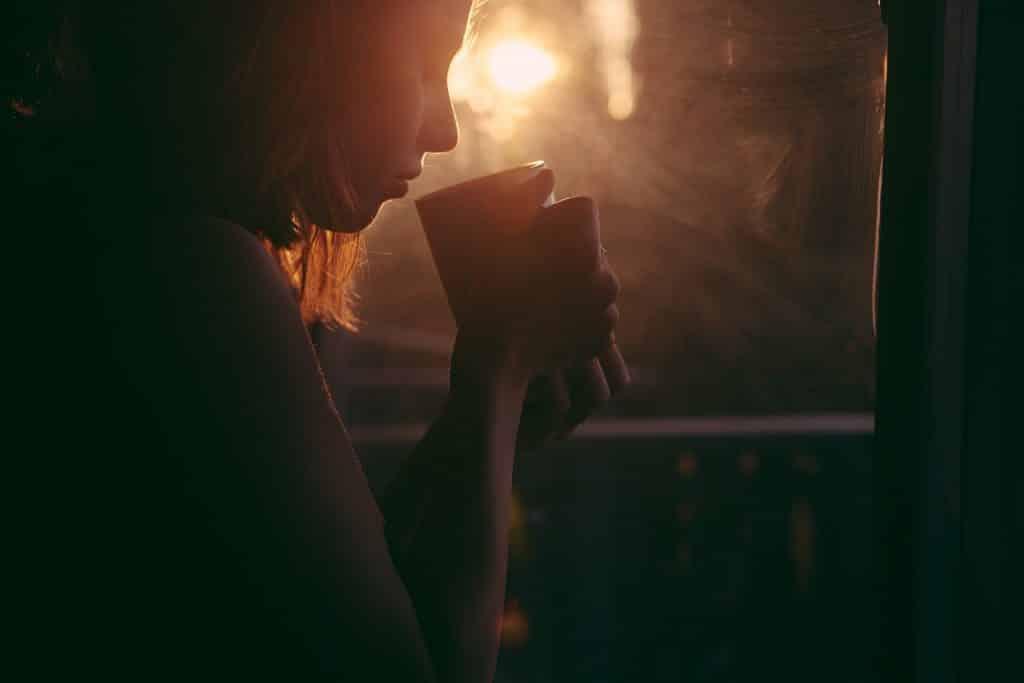 Mulher ao lado de uma janela segurando uma xícara