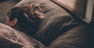 Mulher deitada na cama de olhos fechados