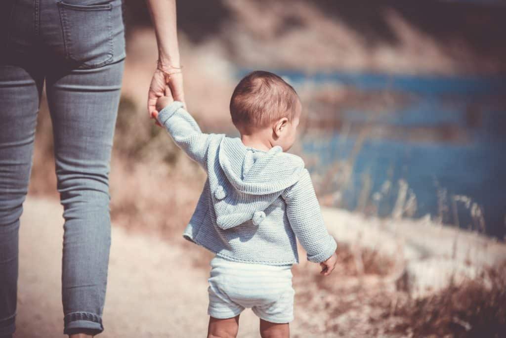 Mulher segurando a mão de uma criança que está olhando para o lago