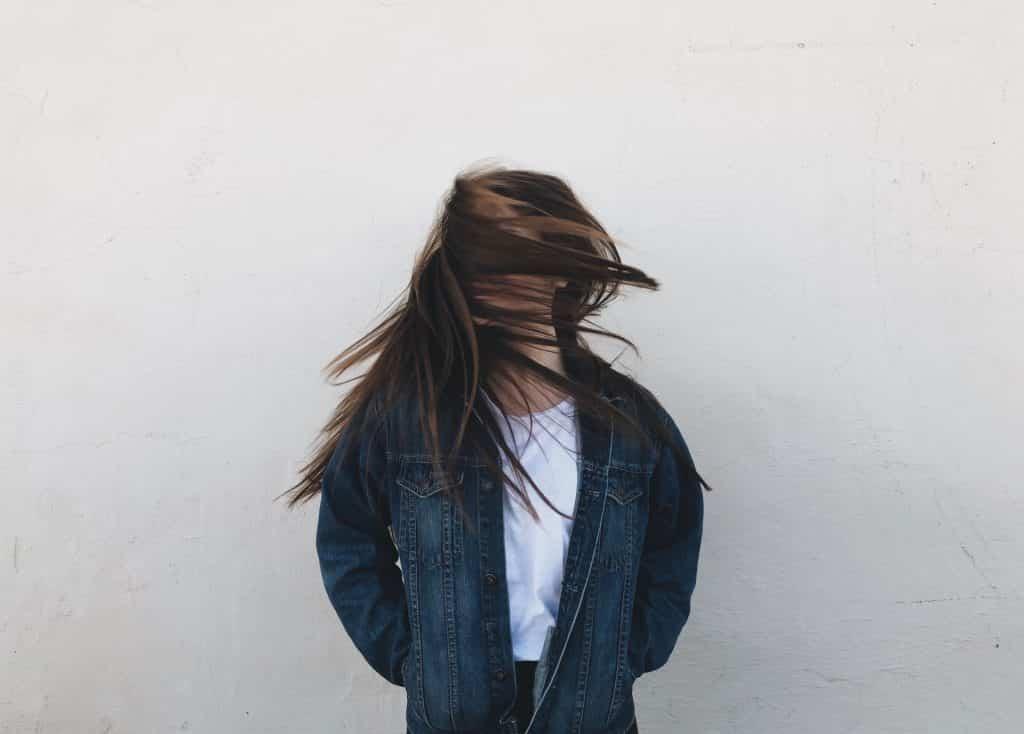 Jovem branca movimentando a cabeça, com cabelos longos e castanhos no rosto