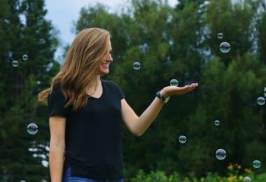 Mulher sorrindo em um jardim e segurando uma bolha de sabão