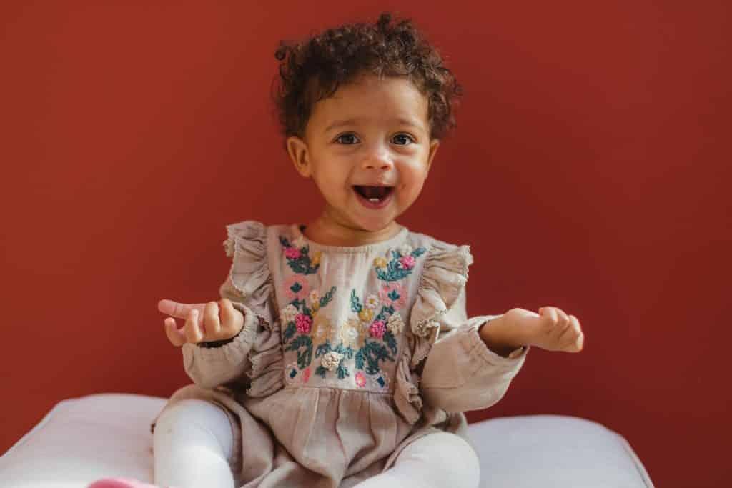 Bebê sorrindo sentada em uma almofada com as mãos levantadas
