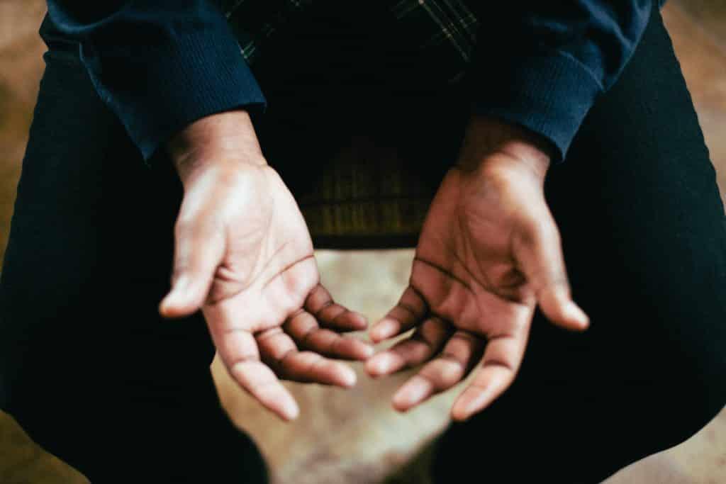 Pessoa sentada com as palmas das mãos voltadas para cima, em sinal de oração.