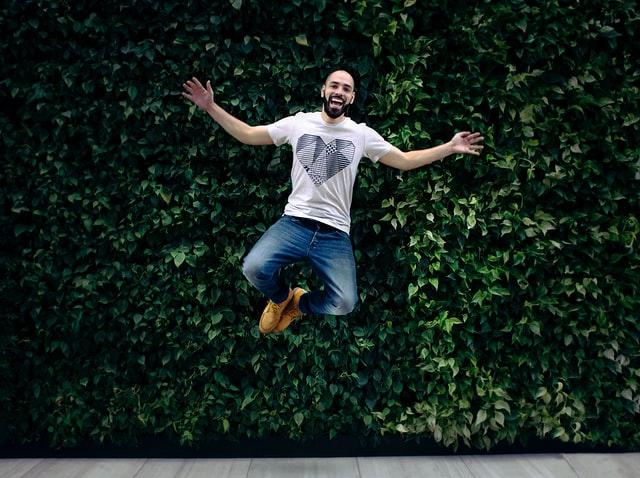 Homem feliz pulando com sorriso e braços abertos