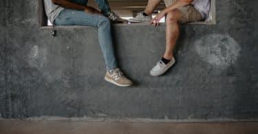 Dois homens sentados em um muro de frente para o outro