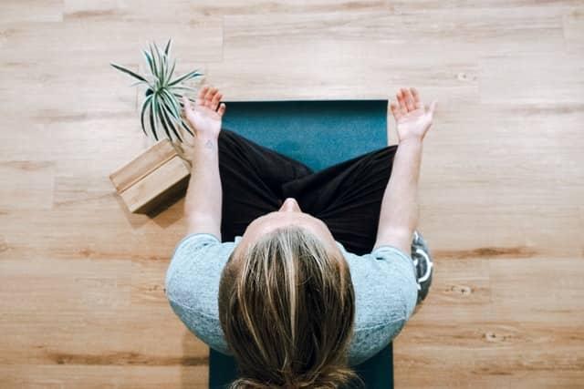 Mulher meditando vista de cima em posição de lótus