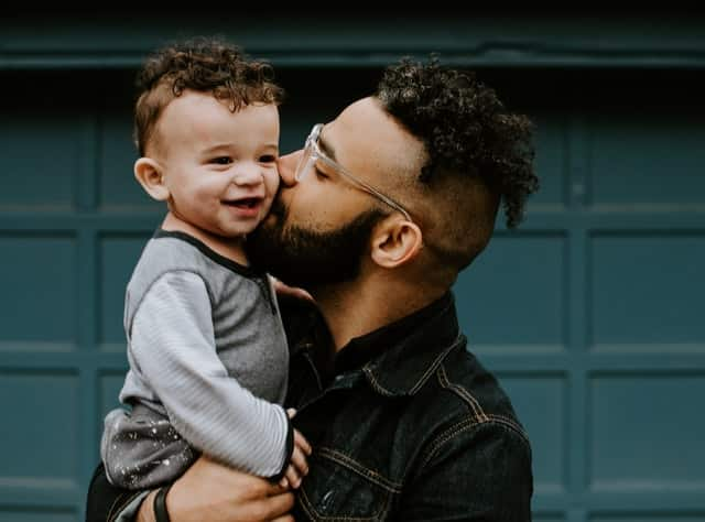 Pai negro beijando bochecha de filho branco
