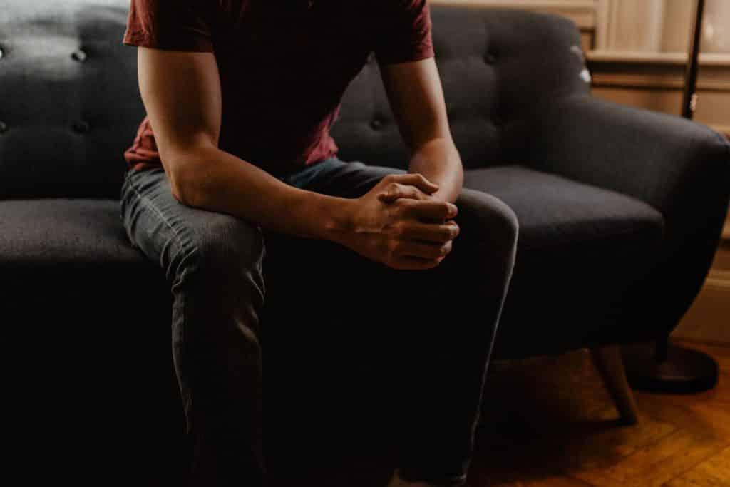 Homem sentado no sofá da sala com as mãos unidas