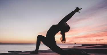 Silhueta de mulher praticando yoga em frente ao mar