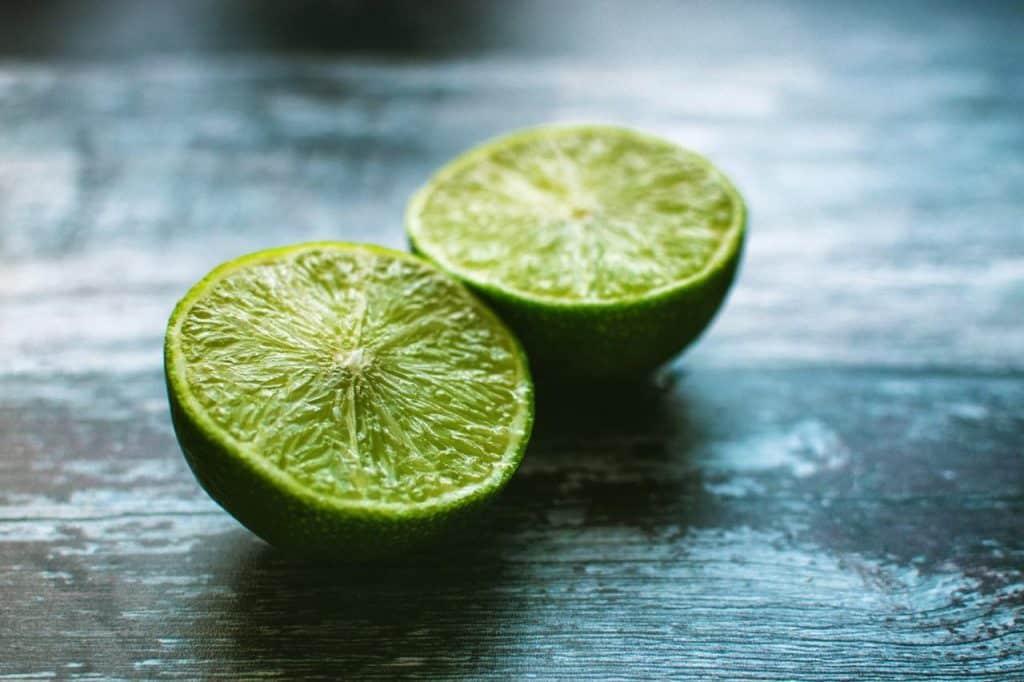 Limão cortado ao meio sobre mesa de madeira.