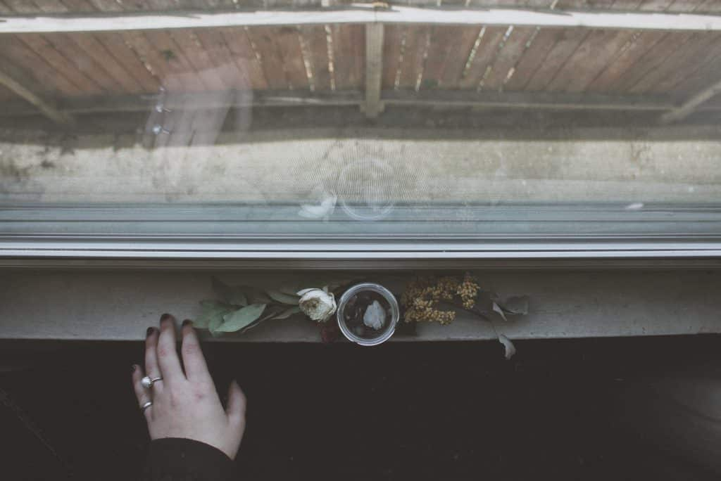 Mão de uma mulher ao lado de uma flor morta na janela