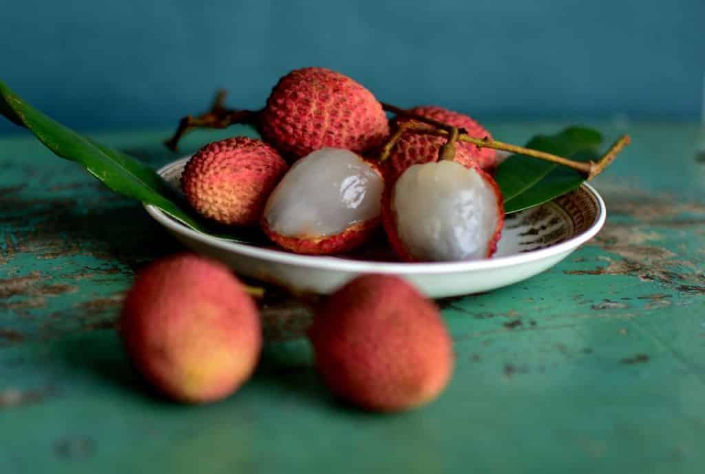 Imagem da fruta lichia. Algumas estão com casca e outras descascadas. Estão dispostas sobre um pires de porcelana.