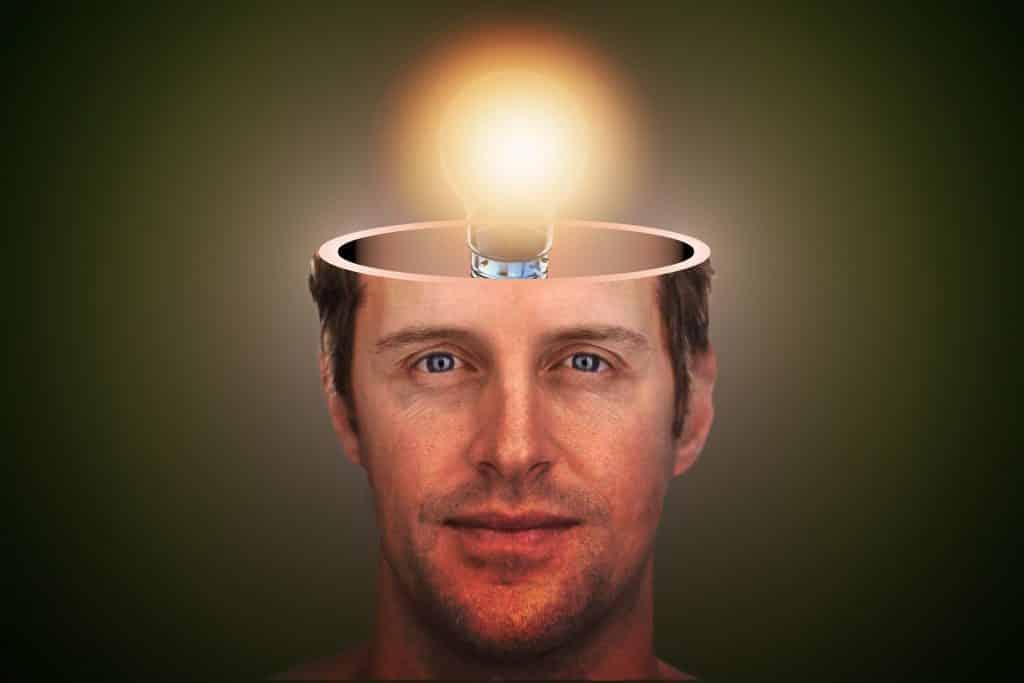 Imagem do rosto de um homem. A parte do cérebro está sendo representada por uma lâmpada acesa que ajuda a esclarecer os seus pensamentos.