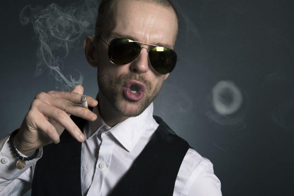 Imagem de um homem usando óculos de sol e fumando um cigarro. Ele tem uma postura arrogante.