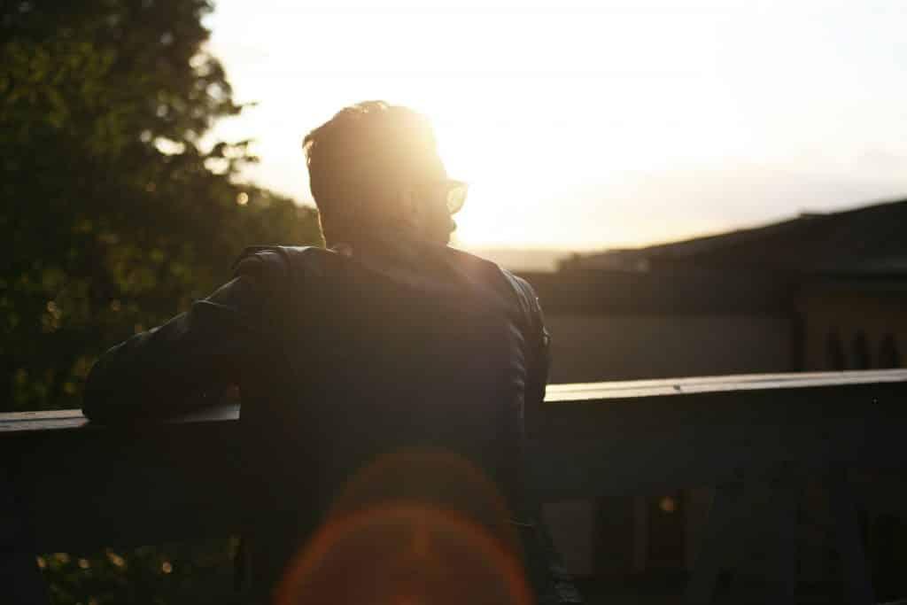Homem apoiando seus braços em um uro olhando para o lado com a luz do sol em seu rosto