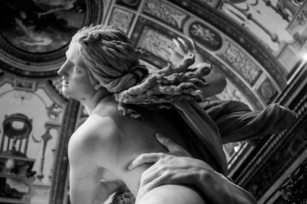 Imagem de uma estátua feminina sendo segurada por uma mão masculina.