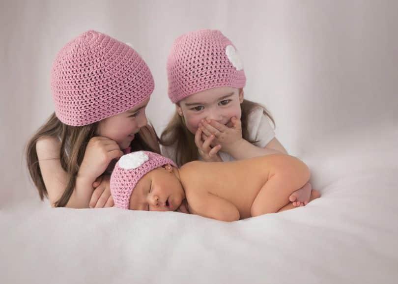 Imagem de três meninas, sendo que uma delas é uma recém nascida. As três usam uma touca rosa de lã.