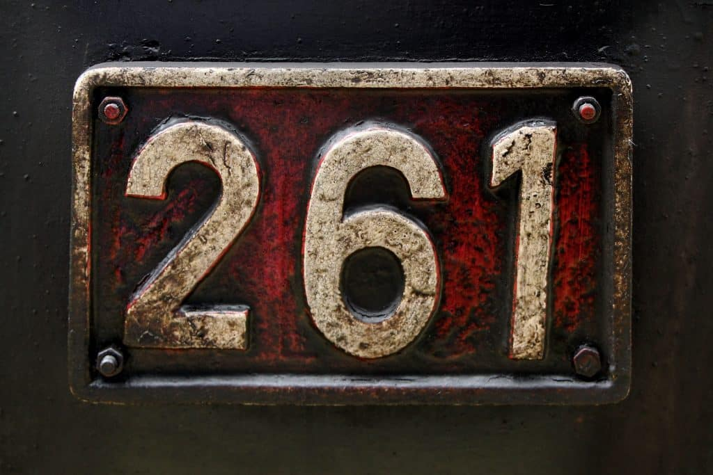 Imagem de uma placa de ferro com o número 261 gravado nela.