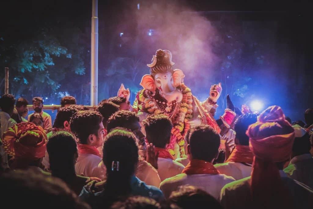 Pessoas em um festival. A estátua de Lord Ganesha está em destaque no meio das pessoas. Está à noite.