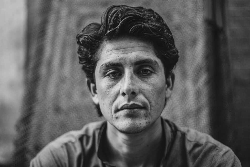 Retrato de um homem de meia idade com expressão triste olhando para frente.