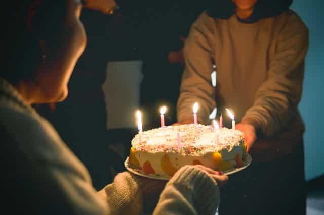 Bolo de aniversário com velas acesas e senhora e filha segurando