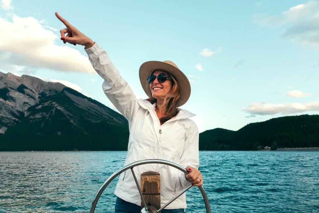 Mulher branca dirigindo barco e com braço esquerdo apontando na diagonal