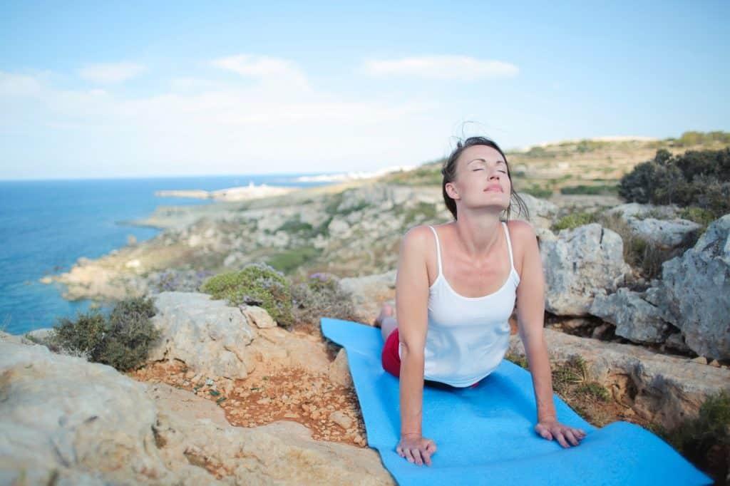 Mulher em uma montanha se alongando em um tapete de yoga.